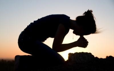 Kvinde knæler med nedbøjet hovede