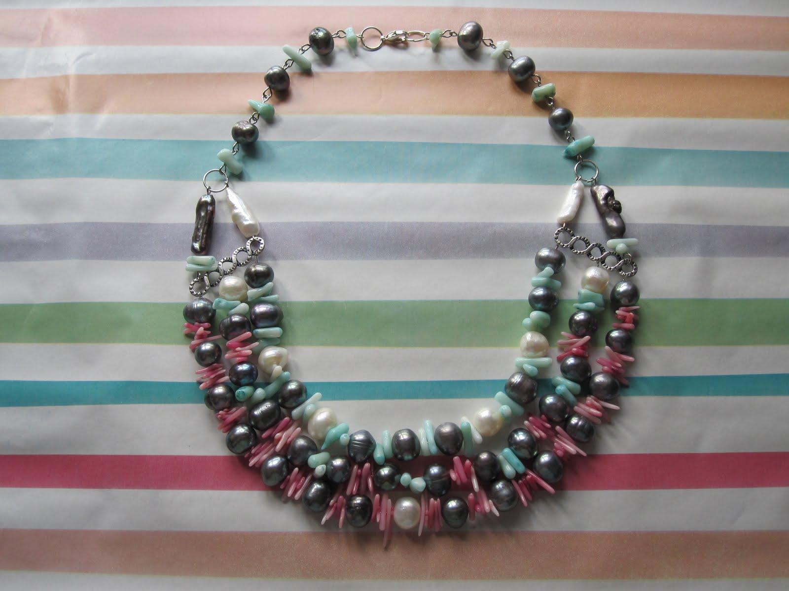 Collar corto en plateado con perlas de río (blancas, negras y alargadas en ambos tonos), coral teñido (fucsia y turquesa) y separadores.