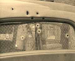 Photo showing bullet holes rear window/death car.. some of which, reportedly fired by Ted Hinton