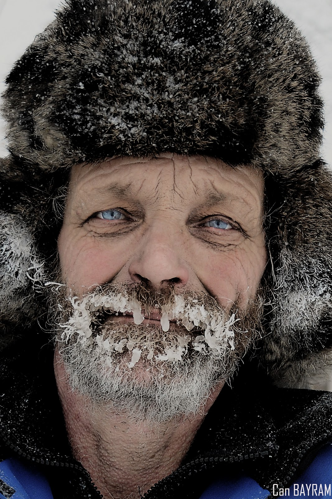 iced beard on a man with blue eyes and a fur hat