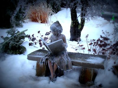 a sculpture of a woman wearing a hat and reading a newspaper or magazine sits frozen on a park bench