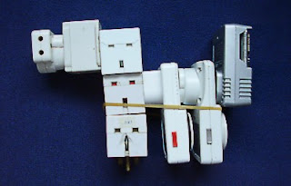 The result of adding haphazardly to a system, illustrated with a stack of mains power adaptors. Don't try this at home.