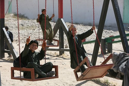 ... a new swing set during recess at the local school house in Musa Qal'eh, ...