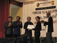 The main individuals of Porsche club giving out a momento