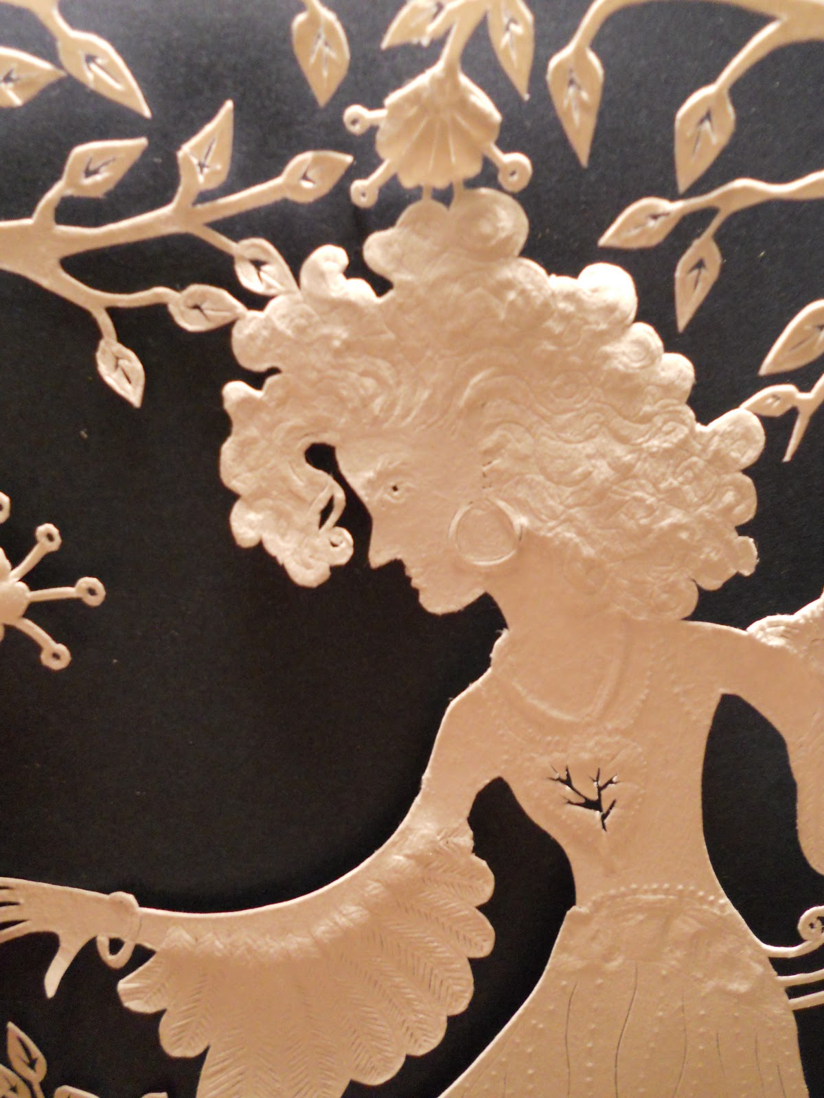 Detail of an embossed paper-cutting depicting a young woman that is ready to take flight and start her own life