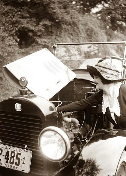 Woman checking auto engine. 1920