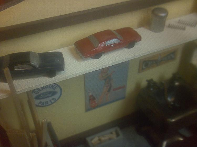 Two diecast cars sit on the shelf