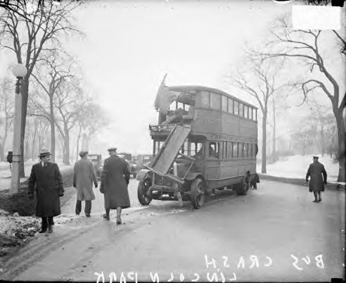 Police officers looking at double-decker bus accident. Chicago 1930