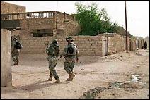 Soldats américains du 1er Bataillon du 502e Régiment d'infanterie en patrouille dans la ville de Mahmoudiyah, le 28 mai 2006. Document AP/Ryan Lenz.