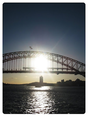 sun setting on the water behind sydney harbour bridge