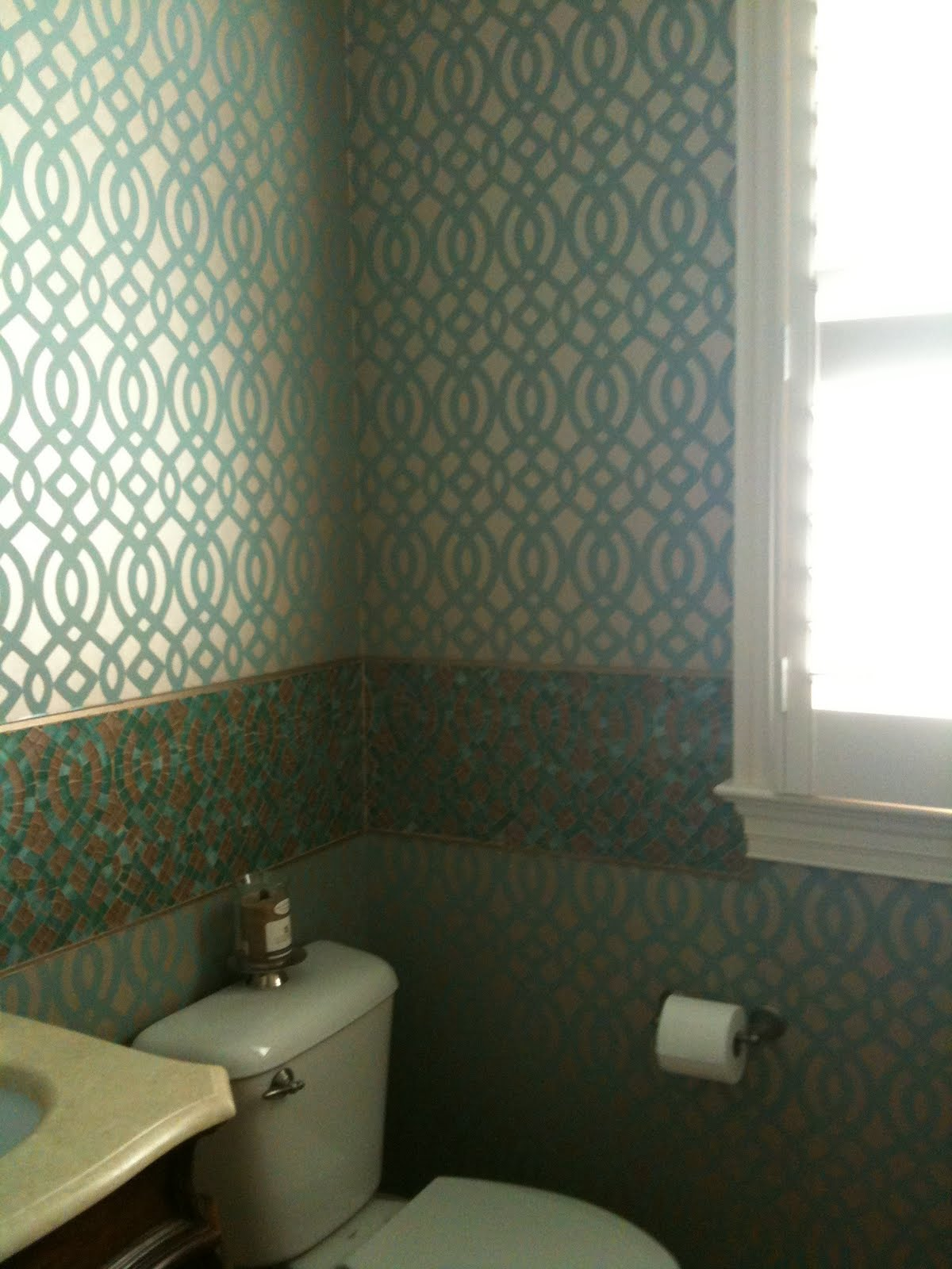 The BEFORE/DURING/AFTER of the transformed powder room shows a custom  backsplash that was designed from the wallcovering that was selected.
