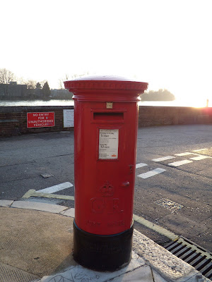 Red British post box by River Thames in Hammersmith