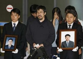 Yoo Kyung-shik (C), one of the released Korean hostages, speaks to media after freed South Korean Christian volunteers, part of a group of 23 missionaries kidnapped in southeast Afghanistan in mid-July, arrived in the Incheon airport in Incheon, west of Seoul September 2, 2007 as two relatives of the two dead Koreans hold portraits of Sim Seong-min (L) and Bae Hyong-kyu. Nineteen South Korean Christian volunteers held hostage by the Taliban in Afghanistan for six weeks returned home on Sunday, thanking their government for winning their release. (REUTERS/Lee Jae-Won)