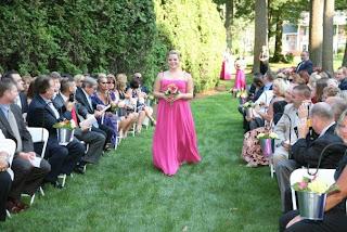 Sam Karwin in her pink bridesmaid dress walking down the aisle