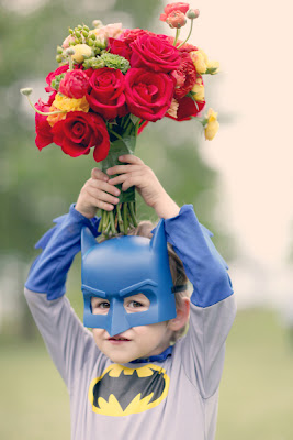 child in Batman costume with bouquet of flowers in hand above his head