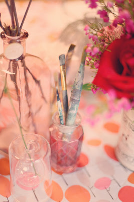 paint brushes stick out of a vase on a tablecloth with large dots