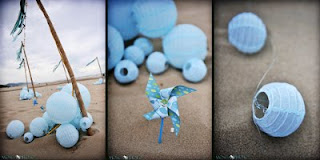 Baby blue paper lanterns with little lights decorate the beach and a blue pinwheel in the sand