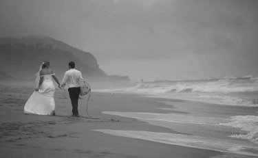 Black and white photo of the bride in her gown holding the hand of the groom, in dress shirt and black pants and carrying his surfboard on the beach
