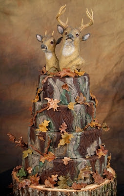 two deer heads on top of a four-tier brown cake with leaves sitting on top a tree stump