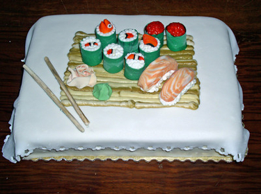 white cake with sushi plate on it with sushi rolls and chopsticks