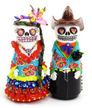 Skeleton bride figurine with long hair and a flower dress next to a skeleton groom with a cowboy hat and poncho