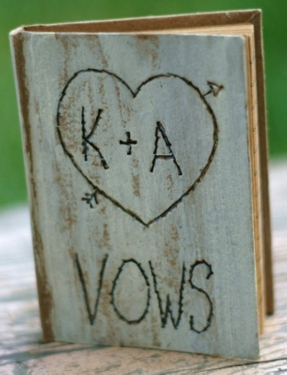 A wooden-looking notepad cover with the word 'vows' and 'K + A' written in a heart with an arrow