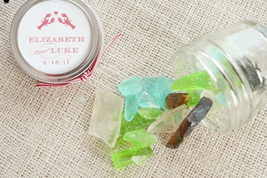 Glass jar with multi-colored sea glass candy spilled out, and a lid next to it that says Elizabeth and Luke, 6-18-11, with two lobsters and a heart