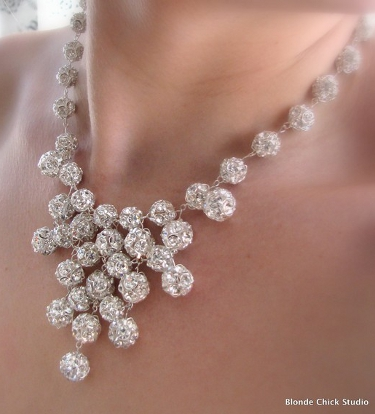 A close-up of a bib-style silver balls necklace on someone's neck