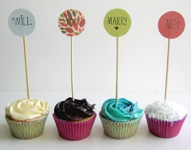 Four individual cupcakes, each with one of the following four words to spell out: Will you marry me?
