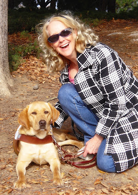 Picture of Wendy and Glenda at a park with the fall leaves all around.  Wendy is in a down and is in harness.  Glenda is one knee and she has a huge smile on her face.