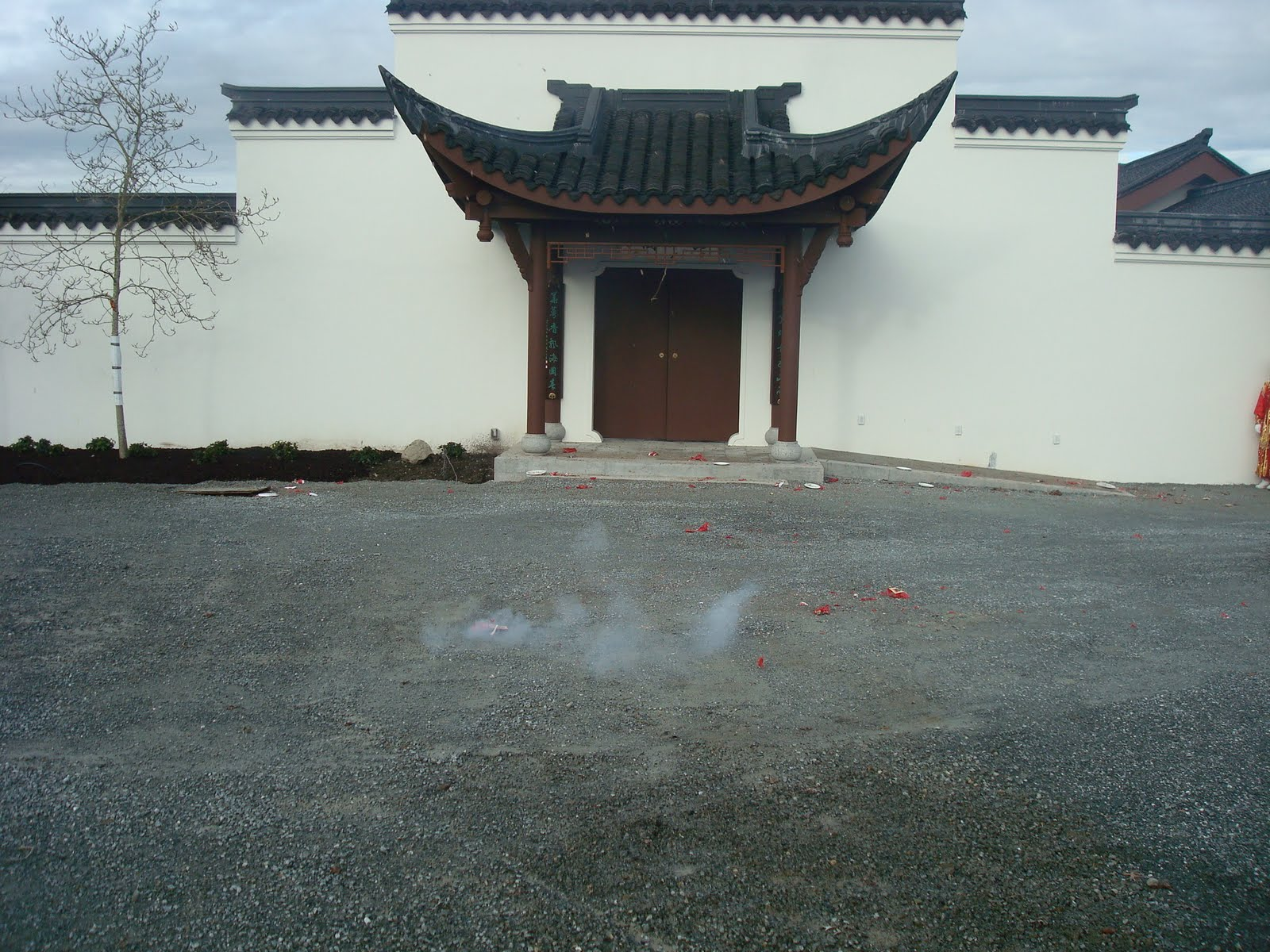 fireworks popping outside the elegant and humble entry gate - Seattle Chinese Garden