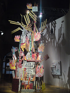 A huge art installation made up of various signs and cut-out flames; the signs have slogans such as BECAUSE I'M NOT WORTH IT, PSYCHIATRIC WARD, FESTIVAL OF CREEPS, and LA DI DA FEED THE POOR LA DI DA CHANGE THE WORLD.