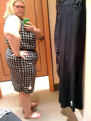 a fat, pale-skinned woman wearing a black and white houndstooth dress. She is turned to the side so you can see the curves of her butt and belly.