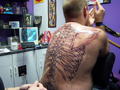 tattoos for men. sketelon back tattoos for men