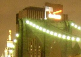 Closeup of Brooklyn Bridge tower with flag at night