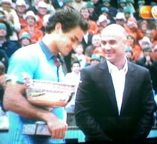 Federer receives the French Open crown from Andre Agassi