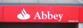 Temporary sign above abbey branch disguising the new Santander sign underneath