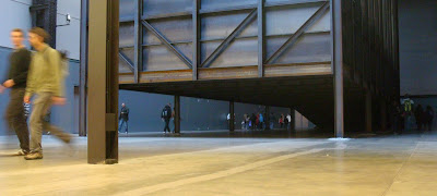 People walking under Miroslaw Balka's box in Tate Modern's Turbine Hall