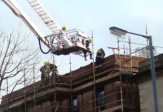 Union Theological College, Belfast - fire brigade platform lifting fire men onto the scaffolding and what remains of the roof
