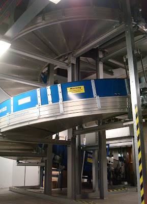 The spiral conveyor belt that brings bags upstairs to be scanned in the dark