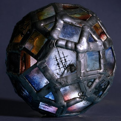 The 'Storm Troubled Sphere' a 75mm diameter bead made from 60 pieces of glass, hand painted with kiln fired enamel.