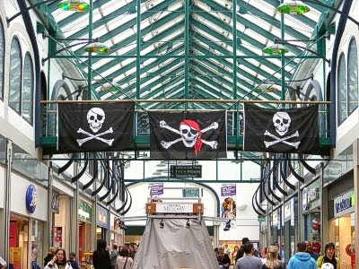 Pirate flags hanging over a passage filled with customers and shop fronts
