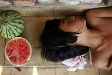 A man sleeps next to his stand selling watermelons ...