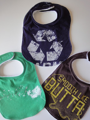 "Shirt bib examples: green with dandelion, blue with recycle symbol, brown with ""smooth like butta"""