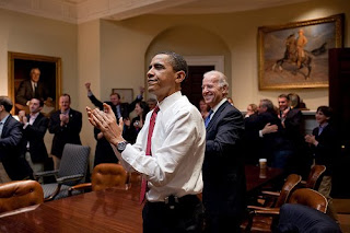 Obama applauding health care vote in oval office with others