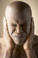 bald, African-American man with eyes and mouth closed tightly and his hands over his ears