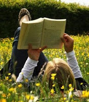 girl reading while lying in field of yellow flowers