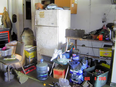 messy Garage with refrigerator and full of crap