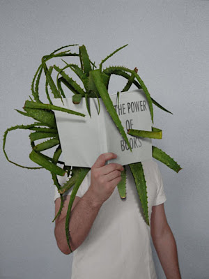 child holding up book entitled the power of books, with aloe leaves coming out of it.