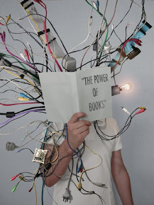 child holding up book entitled the power of books, with wires coming out of it.